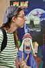 A young woman views the ANI-MA Exhibition walking past Eliya Tsuchida's poster depicting a futuristic version of Noah's Ark. Jerusalem, Israel. 7-May-2012.