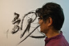 "Artist Kazuo Ishii paints calligraphy for ""Ani-Ma"", 'our soul', on wall adjacent to exhibition at opening ceremony in presence of Shimane Tomoaki, First Secretary and Chief Press and Cultural Attaché, Embassy of Japan in Israel. Jerusalem, Israel. 7-May-2012."