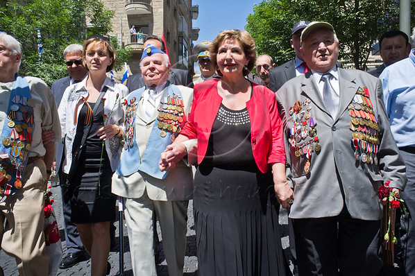 Immigrant Absorption Minister Sofa Landver (in red) holds hands with veterans leading a colorful march celebrating Allied victory over Nazi Germany. Jerusalem, Israel. 9-May-2012.
