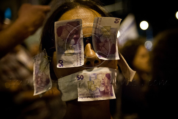A young woman is lead through the demonstration with eyes, ears and mouth covered with monetary bills referring to government alleged attempt to silence the people, deafen and blind them, with a few petty and insignificant reforms. Jerusalem, Israel. 12-May-2012.