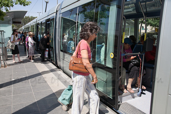 Passengers board Jerusalem Light Rail Transit tram at Herzl Boulevard Yeffe Nof Station. One year into operation daily passenger traffic reaches only 50 percent of expectations. Jerusalem, Israel. 22-May-2012.