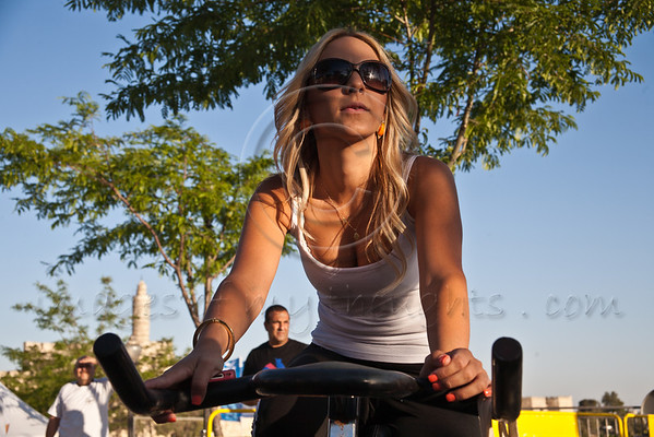 A young blond woman takes part in Jerusalem 2012 Spinning Marathon at the Jaffa Gate. The King David Citadel is viewed behind her to the left. Jerusalem, Israel. 31-May-2012.