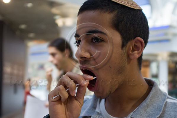 Chen, a young man of Yemenite descent, gives a saliva sample for the stem cell donation registry, to be checked for bone marrow compatibility with patients who require his donation. Jerusalem, Israel. 31-May-2012.