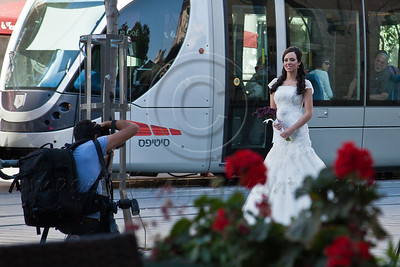 Strange bride goes downtown for a photo-op with the tram before her wedding ceremony. Groom is nowhere to be seen. Jerusalem, Israel. 31-May-2012.