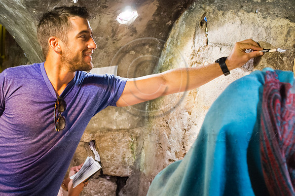 CSI Miami star Jonathan Togo leans to place a note of prayer into a crevice between the stones of the Western Wall in the underground tunnels as a guest of the Tourism Ministry. Jerusalem, Israel. 4-June-2012.