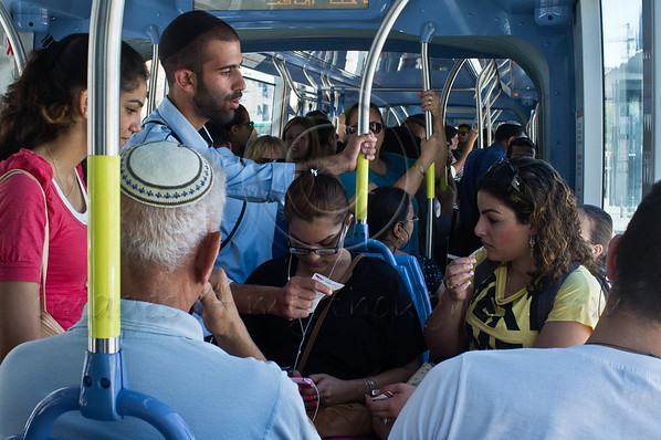 CityPass tram inspector serves a fine to sisters Maayan (L) and Adi Rachamim (R) from Kiryat Gat, tourists in the city and unfamiliar with tram procedures, for having bought four tickets the previous evening, now apparently invalid. Jerusalem, Israel. 12-June-2012.
