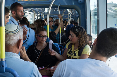 Adi Rachamim from Kiryat Gat, a tourist in the city and unfamiliar with tram procedures, holds up a 180 NIS fine received from tram inspector in disbelief, having bought four tickets the previous evening, now apparently invalid. Jerusalem, Israel. 12-June-2012.