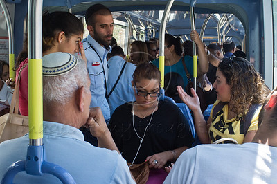 Sisters Maayan (L) and Adi Rachamim (R) from Kiryat Gat, tourists in the city and unfamiliar with tram procedures, argue their case with tram inspectors after having bought four tickets the previous evening, now apparently invalid, and being fined. Jerusalem, Israel. 12-June-2012.