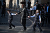 """Ultra-Orthodox Haredi man walks hand-in-hand will two sons, shouting """"Shabess"""" at passing cars, policemen and journalists. Jerusalem, Israel. 23-June-2012."""
