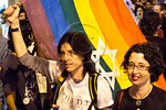 Two gay women march in a social justice demonstration carrying the pride flag with a Jewish Star of David. Jerusalem, Israel. 24-June-2012.