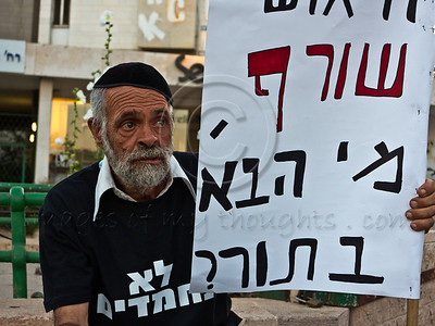 """Demonstrator carries a sign which reads in Hebrew """"Despair burns. Who is next?"""" referring to Moshe Silman, who lit himself up yesterday in Tel-Aviv protesting his social and economical difficulties. Jerusalem, Israel. 15-July-2012."""