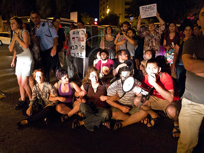 """Social welfare activists, lit by vehicle headlights, sit on King George Street obstructing traffic and chanting """"We are all Moshe Silman!"""". Jerusalem, Israel. 15-July-2012.."""