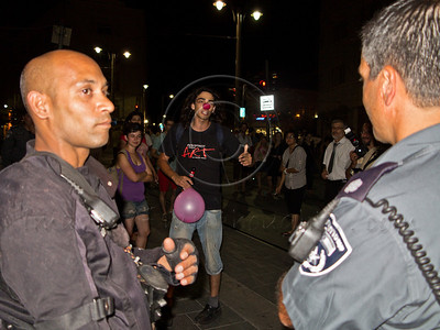 """Man in clown costume tells policemen """"You work for the public. I am the public. You're fired!"""" at a social welfare march. Jerusalem, Israel. 15-July-2012."""