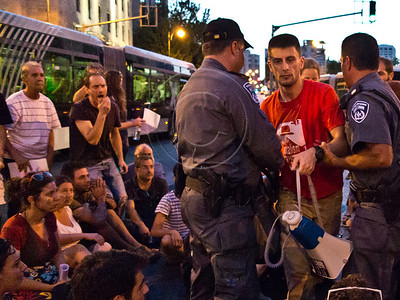 """Police arrest a social welfare activist who incits protesters to obstruct traffic as they sit on King George Street at Kikar paris Square chanting """"We are all Moshe Silman!"""". Jerusalem, Israel. 15-July-2012."""