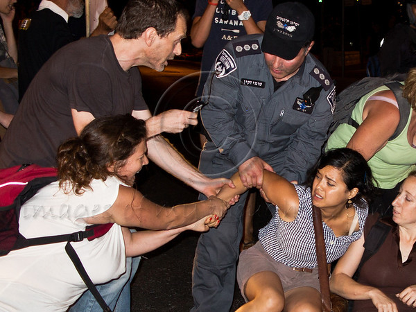A woman cringes in pain as a policeman tries to forcefully break the grasp of her friends and clear her from the street as protesters obstruct traffic on King George Street. Jerusalem, Israel. 15-July-2012.
