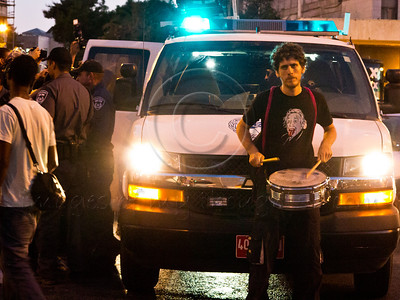 Drummer and activist Uri Agnon blocks a police van with his body to prevent it from leaving the area with an arrested activist inside. Minutes later he himself was arrested. Jerusalem, Israel. 15-July-2012.
