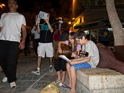 """Social welfare """"March of Rage"""" passes a young girl playing the guitar and collecting donations on Ben-yehuda Street. Jerusalem, Israel. 15-July-2012."""