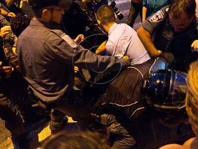 Policemen use force to pry activists from the hold of their friends as they grasp each other sitting in the middle of the street to obstruct traffic and protest for social welfare changes. Jerusalem, Israel. 15-July-2012.