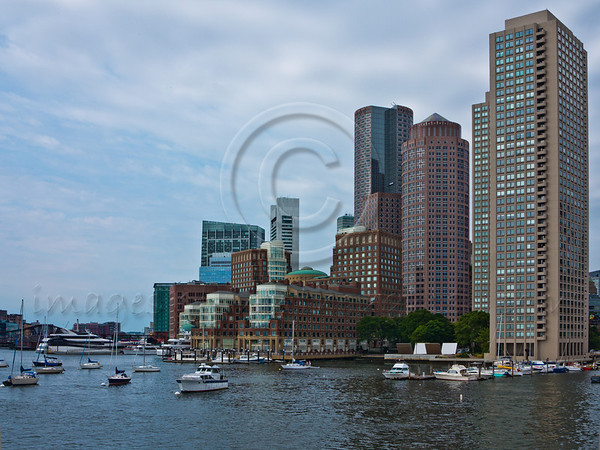 Boston city skyline as viewed from a boat departing to sea for a 3-hour whale watching cruise in Stellwagen Bank Marine Sanctuary. Boston, MA, USA. 19-July-2012.