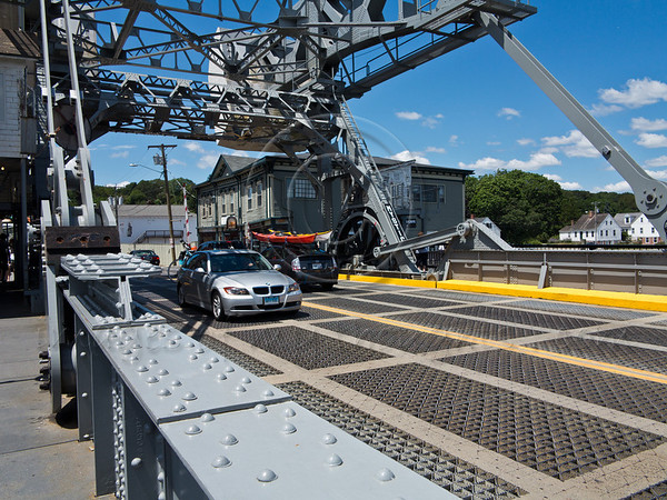 The Mystic River Bascule Bridge is a drawbridge with counterweights designed by Thomas Ellis Brown of New York and built in 1922. it opens approximately 2,200 times per year, with each opening lasting approximately 5 minutes. Mystic, Connecticut, USA. 21-July-2012.<br /> <br /> Mystic seaport is the nation's leading maritime museum consisting of a village, ships and 17 acres of exhibits depicting coastal life in New England in the 19th century.