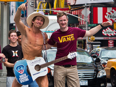 Robert John Burck, known as the Naked Cowboy, poses with an admirer for photos at Times Square. New York, New York, USA. 23-July-2012. New York, the most populous city in the US, the cultural and financial capitals of the world, is overwhelming. Diversity is tremendous and the rhythm and power of the city vertiginous. They say you either love it or hate it - I am still undecided.