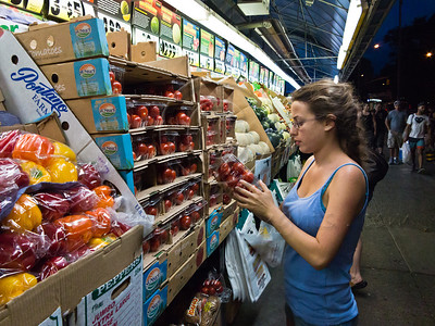 Young woman inspects tomatoes at Fairway Market on Broadway and 74th Street in Upper West Side Manhattan. New York, New York, USA. 23-July-2012. New York, the most populous city in the US, the cultural and financial capitals of the world, is overwhelming. Diversity is tremendous and the rhythm and power of the city vertiginous. They say you either love it or hate it - I am still undecided.