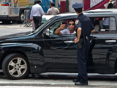 A young male driver in black car converses with policeman. New York, New York, USA. 23-July-2012. New York, the most populous city in the US, the cultural and financial capitals of the world, is overwhelming. Diversity is tremendous and the rhythm and power of the city vertiginous. They say you either love it or hate it - I am still undecided.