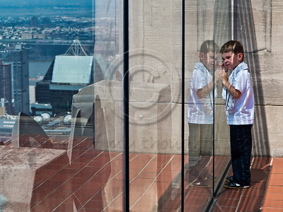 A young boy is reflected in a glass security barrier at Top of the Rock Observation Deck at the Rockefeller Center. New York, New York, USA. 24-July-2012. New York, the most populous city in the US, the cultural and financial capitals of the world, is overwhelming. Diversity is tremendous and the rhythm and power of the city vertiginous. They say you either love it or hate it - I am still undecided.