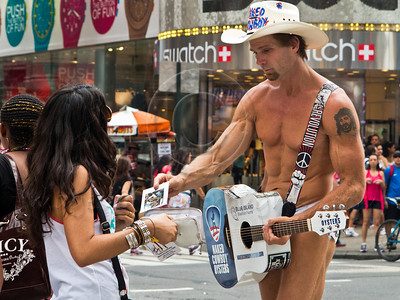 Robert John Burck, known as the Naked Cowboy, hands out a photo postcard to female admirer at Times Square. New York, New York, USA. 23-July-2012. New York, the most populous city in the US, the cultural and financial capitals of the world, is overwhelming. Diversity is tremendous and the rhythm and power of the city vertiginous. They say you either love it or hate it - I am still undecided.