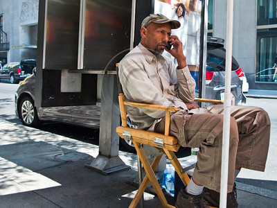 A man speaks on a cell phone sitting on a folding chair in a Manhattan street. New York, New York, USA. 24-July-2012. New York, the most populous city in the US, the cultural and financial capitals of the world, is overwhelming. Diversity is tremendous and the rhythm and power of the city vertiginous. They say you either love it or hate it - I am still undecided.