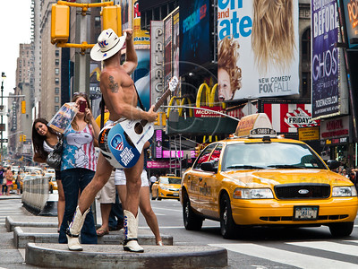 Robert John Burck, known as the Naked Cowboy, poses for photos by admirers at Times Square. New York, New York, USA. 23-July-2012. New York, the most populous city in the US, the cultural and financial capitals of the world, is overwhelming. Diversity is tremendous and the rhythm and power of the city vertiginous. They say you either love it or hate it - I am still undecided.