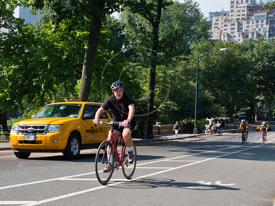 Bike riders alongside a typical NYC yellow taxi in Central Park. New York, New York, USA. 24-July-2012. New York, the most populous city in the US, the cultural and financial capitals of the world, is overwhelming. Diversity is tremendous and the rhythm and power of the city vertiginous. They say you either love it or hate it - I am still undecided.