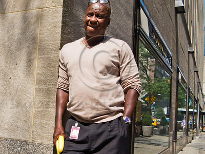 African-American man relaxes on the street holding two bananas. New York, New York, USA. 24-July-2012. New York, the most populous city in the US, the cultural and financial capitals of the world, is overwhelming. Diversity is tremendous and the rhythm and power of the city vertiginous. They say you either love it or hate it - I am still undecided.