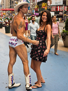 Robert John Burck, known as the Naked Cowboy, with female admirer at Times Square. New York, New York, USA. 23-July-2012. New York, the most populous city in the US, the cultural and financial capitals of the world, is overwhelming. Diversity is tremendous and the rhythm and power of the city vertiginous. They say you either love it or hate it - I am still undecided.