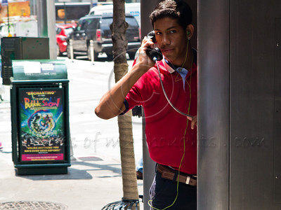 A young man peeks out of a public phone booth. New York, New York, USA. 23-July-2012. New York, the most populous city in the US, the cultural and financial capitals of the world, is overwhelming. Diversity is tremendous and the rhythm and power of the city vertiginous. They say you either love it or hate it - I am still undecided.