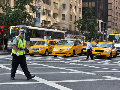 NYPD policeman directs traffic on a busy Manhattan intersection with several typical yellow cabs. New York, New York, USA. 24-July-2012. New York, the most populous city in the US, the cultural and financial capitals of the world, is overwhelming. Diversity is tremendous and the rhythm and power of the city vertiginous. They say you either love it or hate it - I am still undecided.