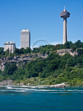 The Skylon Tower (R) is an observation tower that overlooks Niagara Falls from the Canadian side of the Niagara River. It was opened on October 6, 1965 by New York Governor Nelson Rockefeller and Ontario Premier John Robarts. Niagara Falls, Ontario, Canada. 29-July-2012.  Niagara Falls are comprised of three waterfalls between Ontario Canada and New York State on the Niagara River draining Lake Erie into Lake Ontario. Falls form highest flow rate of any waterfall in the world with a drop of more than 50 meters.