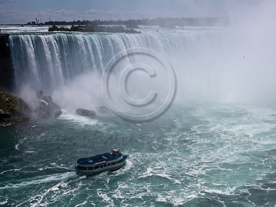 Maid of the Mist boat tours of Niagara Falls, launched in 1846 as a ferry service between Canadian and American sides, take its passengers past the American and Bridal Veil Falls into the dense mist of spray inside the curve of the Horseshoe Falls. Niagara Falls, Ontario, Canada. 29-July-2012.  Niagara Falls are comprised of three waterfalls between Ontario Canada and New York State on the Niagara River draining Lake Erie into Lake Ontario. Falls form highest flow rate of any waterfall in the world with a drop of more than 50 meters.
