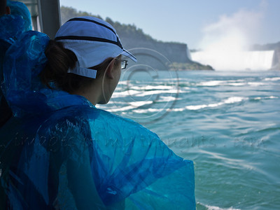 A young woman braves the wet boat tour aboard Maid of the Mist. Launched in 1846 as a ferry service between Canadian and American sides, it take its passengers into the dense mist of spray inside the curve of the Horseshoe Falls. Niagara Falls, Ontario, Canada. 29-July-2012.  Niagara Falls are comprised of three waterfalls between Ontario Canada and New York State on the Niagara River draining Lake Erie into Lake Ontario. Falls form highest flow rate of any waterfall in the world with a drop of more than 50 meters.