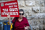 An elderly woman holds up a sign reading ?When the government opposes the people, the people oppose the government? at a demonstration against a strike on Iran. Jerusalem, Israel. 23-Aug ...