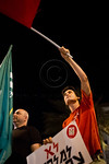 A young man waves a red flag and holds a sign reading ?No to war on Iran? at Paris Square. Jerusalem, Israel. 30-August-2012.  Less than two dozen protest at Paris Square and march to th ...