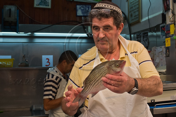 Shop owner displays a bass to customer at Mahane Yehuda Market. Jerusalem, Israel. 4-September-2012.<br /> <br /> Agriculture Ministry estimates more than 1,000 tons of carp will be transformed into Gefilte Fish, a traditional Jewish European dish, patties of deboned, ground, carp, whitefish or pike, and consumed during the upcoming Jewish High Holidays.
