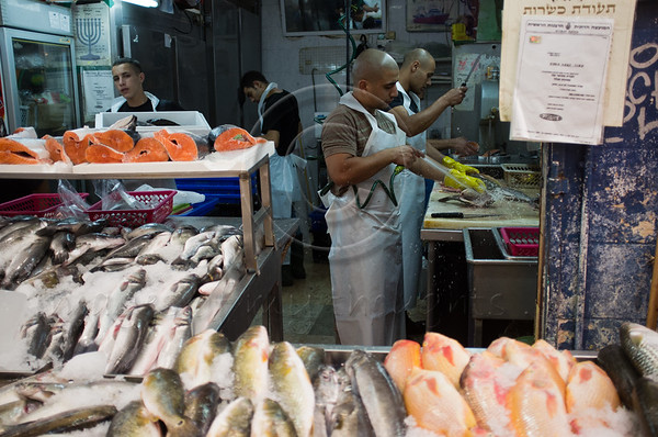 A certificate of Kashrut issued by the Rabbinate is displayed at store entrance (top right) as workers are busy cleaning fish inside. Jerusalem, Israel. 4-September-2012.<br /> <br /> Agriculture Ministry estimates more than 1,000 tons of carp will be transformed into Gefilte Fish, a traditional Jewish European dish, patties of deboned, ground, carp, whitefish or pike, and consumed during the upcoming Jewish High Holidays.