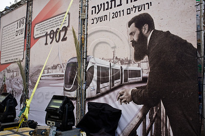 "External Kikar Safra Square municipal sukkah decorations include a classic picture of Theodore Zeev Herzl, considered ""Visionary of the State of Israel"" overlooking today's Light Rail Transit System. Jerusalem, Israel. 30-September-2012.  Last minute preparations underway for the municipal Sukkah at Kikar Safra Square to be opened to the public on Sukkoth, the Feast of Tabernacles, with thousands of visitors expected."