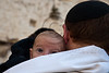 A man attends a special Priestly Blessing service at the Western Wall on Sukkoth with his baby son. Jerusalem, Israel. 3-October-2012.<br /> <br /> Thousands of Jewish pilgrims ascend to the Western Wall on the holiday of Sukkoth, one of three annual pilgrimages, for the Blessing of the Priests, Birkat Kohanim (Hebrew), occurring twice a year.
