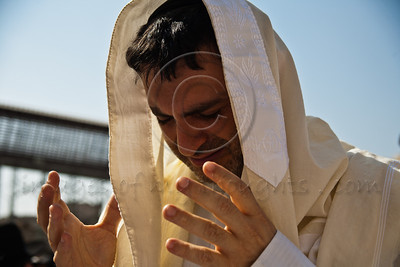 Jewish worshipping men are wrapped in a talit, a traditional prayer shawl, during prayer services at the Western Wall on Sukkoth. Jerusalem, Israel. 3-October-2012.  Thousands of Jewish pilgrims ascend to the Western Wall on the holiday of Sukkoth, one of three annual pilgrimages, for the Blessing of the Priests, Birkat Kohanim (Hebrew), occurring twice a year.