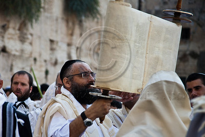 Jewish worshippers raise the Torah in the air having finished reading from it in prayer services at the Western Wall on Sukkoth. Jerusalem, Israel. 3-October-2012.  Thousands of Jewish pilgrims ascend to the Western Wall on the holiday of Sukkoth, one of three annual pilgrimages, for the Blessing of the Priests, Birkat Kohanim (Hebrew), occurring twice a year.