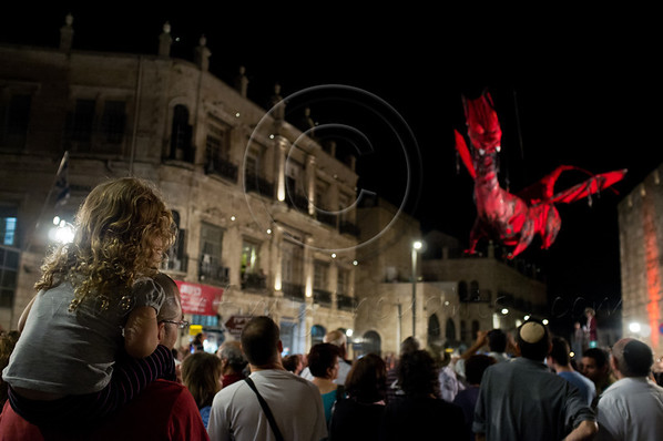 A young girl on father's shoulder watches as a cable-suspended red dragon flies down towards spectators at the Knights of the Night Festival. Jerusalem, Israel. 18-October-2012.<br /> <br /> Third annual Old City Knights Festival opens and will run for four consecutive Thursdays. This year's theme is knights and dragons and features battle scenes between knights and fire spitting dragons, princesses and jesters.