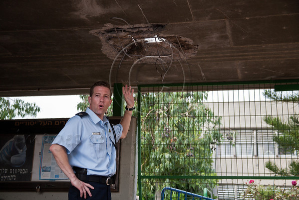Israel Police Spokesman, Micky Rosenfeld, points to the point of penetration of a missile launched from Gaza through the concrete ceiling of a school yard. Ashkelon, Israel. 19-Nov-2012.<br /> <br /> Palestinian launched rocket makes a direct hit in an Ashkelon school courtyard exploding through a concrete ceiling and creating a small crater. Miraculously, due to IDF Home Front Command instructions, schools are out in the Gaza perimeter.