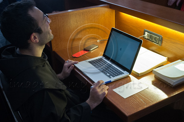 A young Franciscan monk is busy studying in the Franciscan Terra Sancta compound library using an Apple Mac Book and with an iPhone on the desk to his left. Jerusalem, Israel. 30-Nov-2012.<br /> <br /> Of the 20,000 Franciscan monks worldwide about 300 reside in Israel as well as some 1,000 nuns. Saint Francis Francesco of Assisi first arrived in the Holy Land in 1219 and they have been custodians of the holy sites ever since.